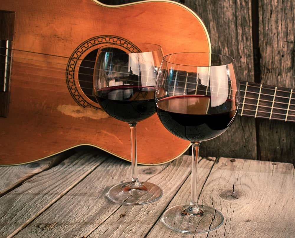 Two wine glasses and a guitar